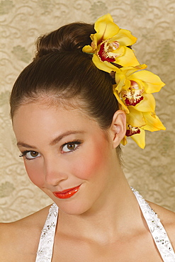 Hawaii, Portrait of young woman with orchids in hair.