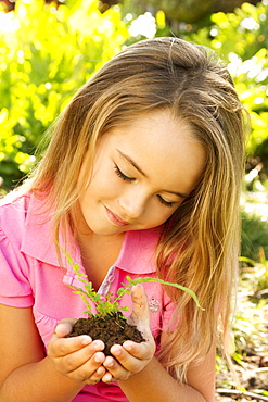 Hawaii, Young girl holding fern seedling in mound of dirt.