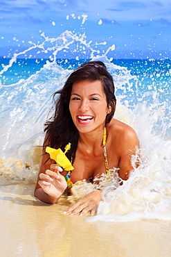 Hawaii, Oahu, Lanikai, Beautiful woman on the beach holding a yellow hibiscus with wave crashing on her.
