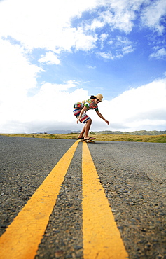 Hawaii, Oahu, Young male riding a skateboard on the roadway.