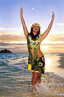 Hawaii, Oahu, Lanikai, Female hula dancer along beach shoreline at sunrise.