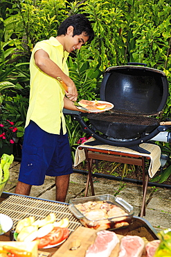 Hawaii, Young man preparing Outdoor barbecue feast in Hawaii garden.
