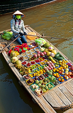 South East Asia, Vietnam, Ha Long Bay, Vietnamese woman sells fresh fruit from her small boat.