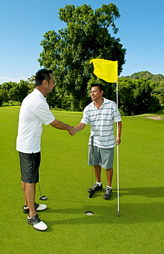 Hawaii, Oahu, Honolulu, Pali Golf Course, A local golfer congratulates his friend after making a good shot at hole 5.