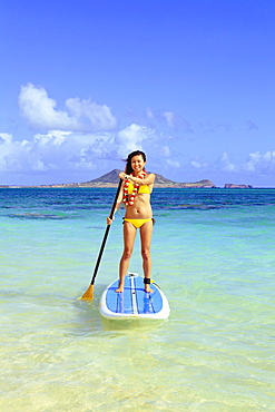 Hawaii, Oahu, Lanikai, Asian women paddle boarding off the beach near Mokulua Island.