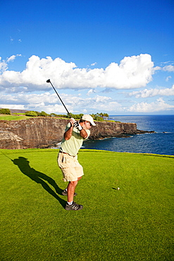 Hawaii, Lanai, Man hitting a tee shot on The Challenge at Manele golf course.