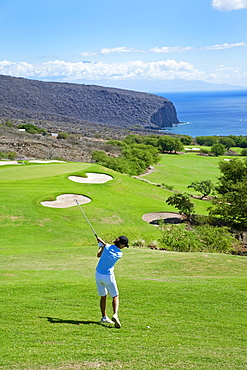 Hawaii, Lanai, Woman hitting a tee shot on The Challenge at Manele golf course.