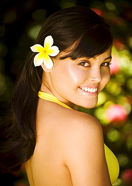 Hawaii, Oahu, Beautiful headshot of a young girl with a plumeria in her ear.