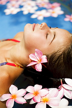 Hawaii, Oahu, Young girl resting in a pool with plumerias.