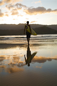 Hawaii, Kauai, Hanalei Bay, young man at the beach walking with surfboard at sunset.