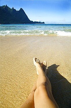 Hawaii, Kauai, Tunnels,  Womans legs relaxing on the sand.