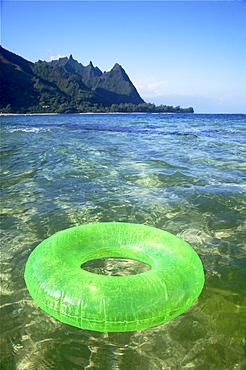 Hawaii, Kauai, Tunnels beach, Green innertube on the water.