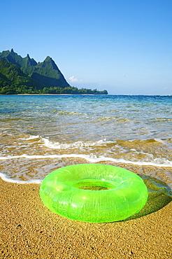 Hawaii, Kauai, Tunnels beach, Green innertube on the beach.