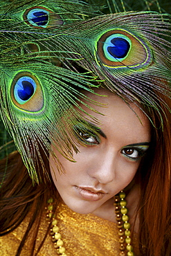 Hawaii, Oahu, Headshot portrait of Beautiful Gorgeous Young Girl with Peacock Feathers near her face wearing matching makeup, fabric and necklace.