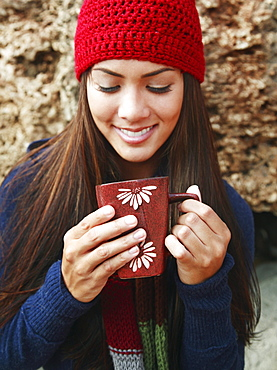 Hawaii, Oahu, Young woman outside in cozy winter weather drinking coffee.