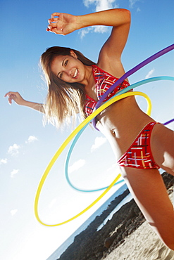 Hawaii, Oahu, Attractive young woman on the beach hula hooping.