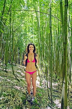 Hawaii, Maui, Hana, Woman hiking in a bamboo trail.