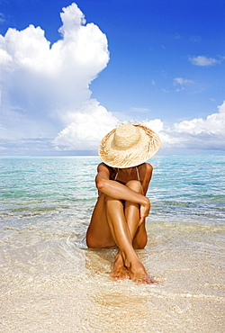 Hawaii, Woman sitting in the ocean at a remote tropical location.