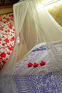 French Polynesia, Tahiti, Maupiti, hotel bedroom with flowers on bed.