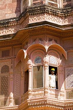 India, Rajasthan, Jodhpur, Fort Mehrangarh, man in window of Fort Palace.