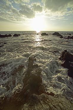 Hawaii, Big Island, Kohala Coast, Sunset and surf on rocks.