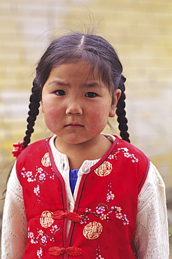 Mongolia, Ulaanbaatar, Small young local girl wearing red vest.