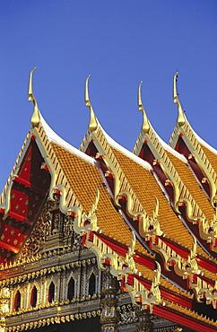 Bangkok, Thailand, Wat Benjamabophit (Marble Temple) top of gold trimmed temple, blue sky.