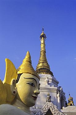 Burma (Myanmar), Yangon, Schewedagon Paya, close-up of Buddha statue and top of temple against blue sky.