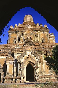 Burma (Myanmar), Old Bagan, Htilominlo Temple framed view from gateway, blue sky.