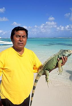 Mexico, Yucatan Peninsula, Cozumel, Local man on beach holding Iguana.
