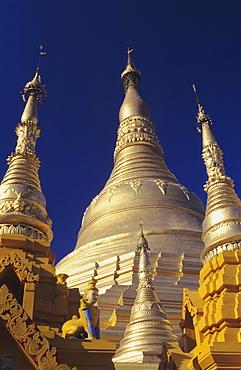Burma (Myanmar), Yangon, Shwedagon Paya, close-up of three golden steeples in sunlight.