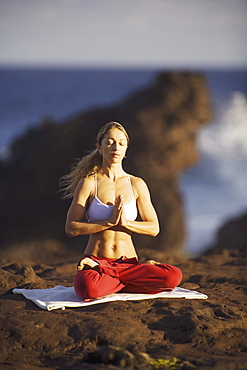 Hawaii, Maui, young woman doing yoga next to the ocean.