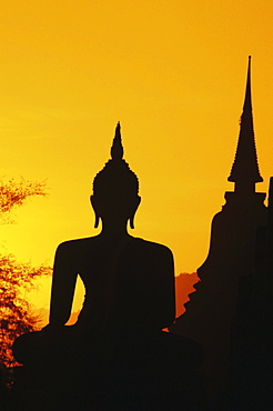 Thailand, Sukhothai, Buddha and temple silhouetted at sunset, orange sky