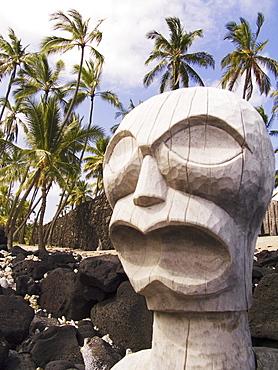 Hawaii, Big Island, Puuhonua O Honaunau, City of Refuge, Ki'i against blue sky and palm trees.