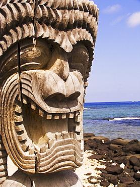 Hawaii, Big Island, Puuhonua O Honaunau, City of Refuge, Close-up of Ki'i in front of blue sky and ocean.
