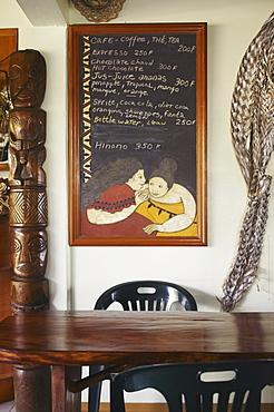 French Polynesia, Tahiti, Huahine, Inside a coffeeshop, decorative wooden table, chalkboard menu on wall