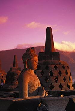 Indonesia, Java, Borobudor Temple and Buddha statue at sunrise, pink misty sky