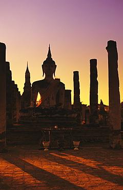 Thailand, Sukhothai, Wat Mahathat, Buddha and pillars backlit at sunset