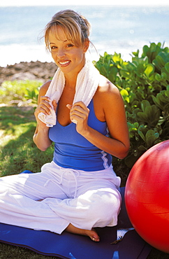 Woman sitting in yoga position near ocean on mat with red exercise ball
