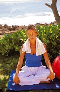 Caucasian woman sitting on yoga mat near ocean meditating in sunlight