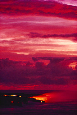 Hawaii, Big Island, Hawaii Volcanoes National Park, Lava flows into ocean, bright red sunset.