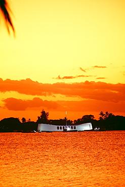 Hawaii, Oahu, Pearl Harbor, Full view of Arizona Memorial at sunset, bright orange yellow sky
