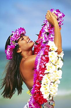 Hawaiian woman wearing haku and holding leis on beach.