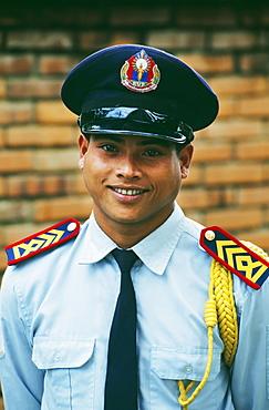 Laos, Luang Prabang, Portrait of a uniformed security guard.