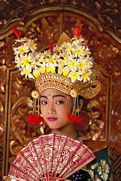 Indonesia, Bali, Legong Dancer young girl in traditional costume, holding fan
