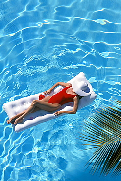 Woman floats in pool on raft, white hat