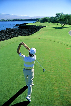 Hawaii, Big Island, Kohala, Mauna Lani Golf Course, 7th Tee, Honokaape tee off, view from behind man swinging A18A. EDITORIAL USE ONLY.