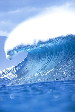 Huge translucent blue wave curling with wind spray, shimmery water