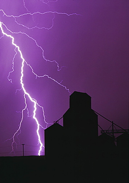 Agriculture - A bolt of lightning lights up the night sky during a storm silhouetting a grain elevator / Manitoba, Canada.