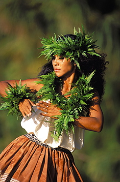 Hawaii, Outdoor Front Angle Of Woman Dancing Hula, Wearing Fern Haku, Lei And Kupe'e Blurry Background